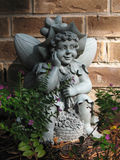 Garden Fairy. A Garden Fairy sits in rest and enjoys a freshly picked bouquet of flowers Royalty Free Stock Photography