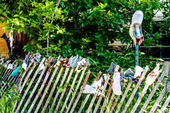 Garden Fence of Old Shoes, Boots and Gloves. Old wooden garden fence filled with worn shoes, boots and gloves Royalty Free Stock Photos