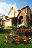 Garden with flowers in front of new cottage. Garden with beautiful flowers in front of new two-storied brick cottage Stock Images