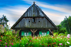 Garden with flowers in front of the old wooden hut Stock Photo