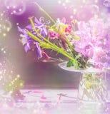 Garden flowers in glass vase in sunlight and bokeh Stock Image