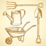 Garden fork, barrow, watering can and shovel,  background Stock Images