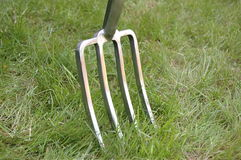 Garden fork inserted into lawn Royalty Free Stock Images