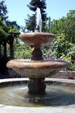 Garden Fountain. A flowing water fountain surrrounded by a garden of flowers royalty free stock images
