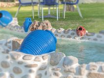 Garden fountain with blue ceramic jar on summer jar with rock Stock Images