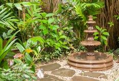 Garden fountain. Stone water fountain, green garden Royalty Free Stock Photo