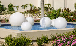 Garden fountain with white spheres lights floating in water Stock Image