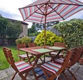 Garden furniture. Foldable wooden garden furniture with striped umbrella Stock Photo