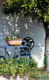 Garden furniture. A garden table and chair with potted flowers under a tree Royalty Free Stock Photography