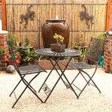 Garden furniture. Wrought iron chairs and table with succulent and brown wall Royalty Free Stock Photography