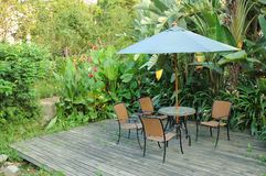Garden furniture. Rattan chairs and table under umbrella on a wooden floor by the banana trees background in garden Royalty Free Stock Photo
