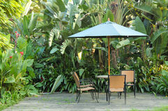 Garden furniture. Rattan chairs and table under umbrella on a wooden floor by the banana trees background at garden Royalty Free Stock Image
