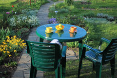 Garden furniture among flowers near garden path of flagstones. There are two chairs and table. On table are cups, saucers, teaspoons and bowl of fruit Stock Photo