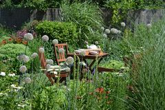 Garden furniture. Outdoor garden chairs and small table in the flowers garden royalty free stock image