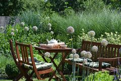 Garden furniture. Outdoor garden chairs and small table in the flowers garden stock photos
