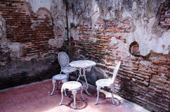 Garden furniture set with old brick wall Royalty Free Stock Photo