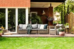 Garden furniture in the summer. Grey pillows and blanket on garden furniture in front of a house in the summer stock photo