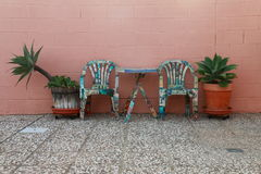 GARDEN FURNITURES. Garden furniture and plants in front of a colored wall salmon Stock Photos