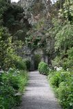The garden gate. This garden features an ornate iron gate at the end of the pebbled path stock photos