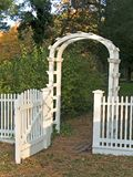 Garden Gate. A white garden gate and picket fence along with a cobblestone walkway royalty free stock photography