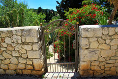 Garden Gate. Colourful garden gate with stone wall Stock Images