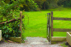 Garden Gate. A rustic wooden garden gate opening to a lush green lawn royalty free stock photos