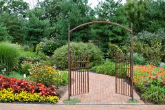 Garden Gate. Beautiful floral garden with decorative wrought iron gate royalty free stock photo