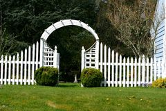 Garden gate. White picket fence, garden gate arbor and trellis royalty free stock photography