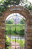 Garden Gate. View looking through a country cottage garden gate with a view of Salisbury Cathedral in distance. Gate surrounded by a brick constructed arch Stock Photo