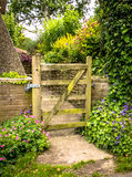 Garden Gate. Guarding the entrance to a mature, pretty garden path planted with a variety of shrubs and flowers Stock Image