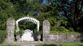 Garden Gate with Stone Wall. White garden gate and arbor with old stone wall stock photography