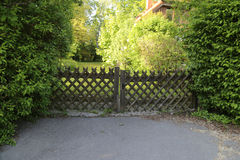Garden gate. A very nice  gate made of metal for a beautiful garden in a summer sunny day and inside seen a house Stock Photo