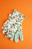 Garden gloves. On a orange background Royalty Free Stock Photo
