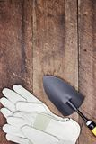Garden Gloves and Hand Trowel. Garden gloves and hand spade over a rustic wooden table. Image shot from above in flat lay style Stock Photography