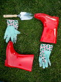 Garden gloves, spade and red rubber boots lying on green grass Stock Photos