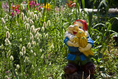 Garden gnome. Among summer flowers Royalty Free Stock Image