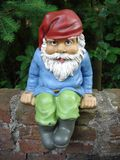 Garden gnome. A garden gnome sitting on a wall Stock Images