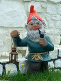Garden Gnome. Holding a light and smoking Royalty Free Stock Images