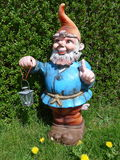Funny garden gnome with a lantern stock images