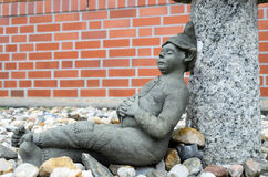 Garden Gnome at lunch break. Stone garden gnome at the lunch break before the background of stones Stock Photo
