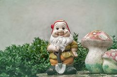 Garden gnome and mushroom. Garden gnome with a showel in hand close to a big mushroom Stock Images