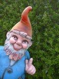 Funny garden gnome. Garden gnome peeps around the corner stock photos