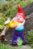 Garden gnome playing a horn in a garden Royalty Free Stock Photo