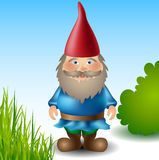Garden gnome. With red hat between grass and bush Royalty Free Stock Photography
