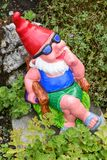 Garden gnome sitting in a chair on a garden Royalty Free Stock Photography