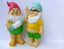 Two funny garden gnomes with swimming ring and sunglasses. Two funny garden gnomes with sunglasses makes peace sign This figure has NO recognizable mark and is royalty free stock photo