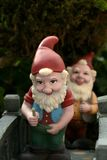 Garden Gnomes. Two happy Garden Gnomes crossing a bridge stock photo