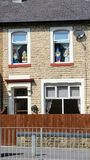 Garden gnomes inside of the house. Four garden gnomes inside of the house looking trough the window in colne, england royalty free stock photo