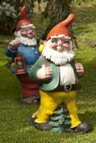 Garden Gnomes in the Swiss Alps. Two colorful, wooden garden gnomes in traditional costumes in the Swiss Alps royalty free stock image