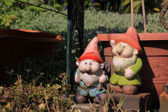 Garden Gnomes 2. Two garden gnomes in a city garden set next to a garden bench and in front of a teracotta coloured plastic plant pot. Set on a landscape format stock photo